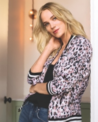 woman in black, white and light pink leopard print bomber jacket and jeans