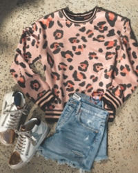 pink and black animal print sweatshirt and light wash distressed jean shorts