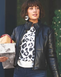 woman in black leather jacket, animal print sweater, jeans and statement earrings carrying holiday gifts