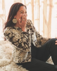 woman in animal print faux fur jacket, with black pants and statement earrings