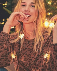woman in brown animal print sweater with holiday lights around her neck in front of a christmas tree