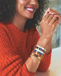 woman in red sweater wearing a colorful stack of bracelets