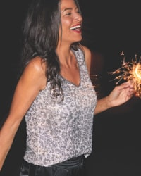 woman in silver leopard print sparkling v-neck tank top and black vegan joggers while holding festive sparklers
