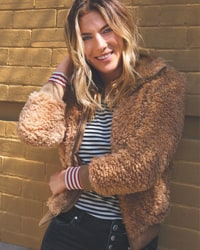 woman in light brown teddy bear fuzzy jacket, black and white stripe top and black high-rise denim