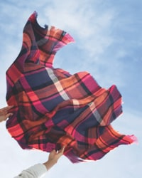 scarf blowing in the wind below a blue fall sky