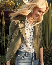 women in olive green utility jacket with print top underneath and high-rise denim