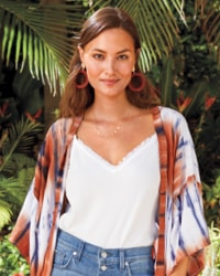 woman in red statement hoop earrings with a simple gold necklace, wearing a kimono, white tank and jeans