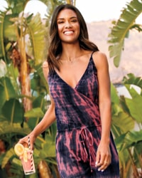 woman in navy and pink tie-dye jumpsuit in tropical location