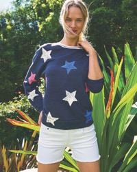 woman in star graphic sweater and white shorts