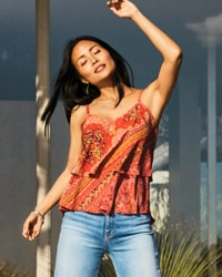 woman wearing orange patterned cami and jeans