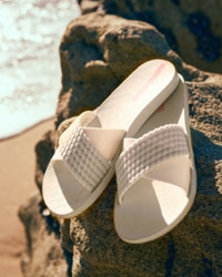 Lifestyle shot of light pink slide on sandals on the beach